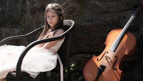 Beautiful girl in a pink dress sits in a chair with a cello