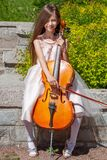Beautiful girl in a pink dress sits in nature with a cello