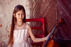 Beautiful girl in a pink dress sits on a red chair with a cello