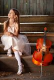 Beautiful girl in a pink dress sits on the steps with a cello in a country house