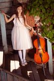 Beautiful girl in a pink dress stands with a cello and a bow near the wall of the house with wild grapes