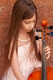 Beautiful girl in a pink dress stands with a cello in the city against the wall