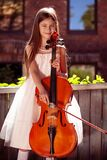 Beautiful girl in a pink dress stands with a cello in a country house