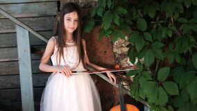 Beautiful girl in a pink dress stands with a cello in a country house with wild grapes