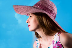 Beautiful girl in a pink hat from the sun in a profile on a blue Royalty Free Stock Image