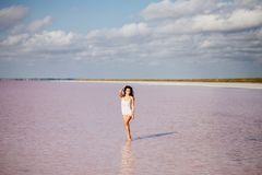 Beautiful girl on a pink lake. Beautiful girl on a pink salty lake. Beautiful figure. Reflection in water royalty free stock image