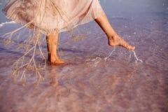 Beautiful girl on a pink lake. Beautiful girl on a pink salty lake. Beautiful figure. Reflection in water stock photography