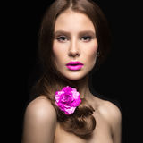 Beautiful girl with pink lips and a rose in her hair. Beauty face. Royalty Free Stock Photography