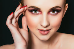 Beautiful girl with pink make-up and smooth skin close-up on a dark background Stock Image