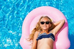 Beautiful girl on pink mattress in swimming pool Stock Photos
