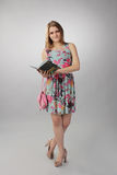 Beautiful girl in pink posing with a book, a Business lady. Royalty Free Stock Image