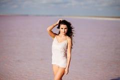 Beautiful girl on a pink lake. Beautiful girl on a pink salty lake. Beautiful figure. Reflection in water royalty free stock photos