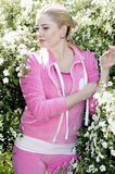 The beautiful girl in a pink suit among the blossoming bush Stock Photo