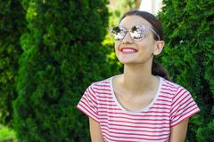 Beautiful girl in pink sunglasses over park background stock photo