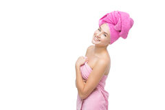 Beautiful girl in pink towel. Beautiful young woman with hair and body wrapped in pink towel. Isolated over white background. Copy space Royalty Free Stock Images