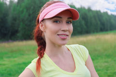 Beautiful girl in the pink visor is surrounded by nature an Royalty Free Stock Photo