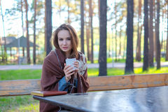 Beautiful girl in a plaid drinking coffee in the park Stock Photo