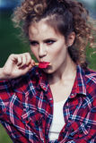 Beautiful girl in plaid shirt eats ice cream outdoors. Stock Photos