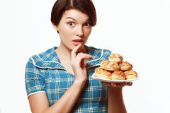 Beautiful girl with a plate of bakery products, diet, calories. Beautiful and sweet girl wants to eat a patty with sesame, diet Royalty Free Stock Image