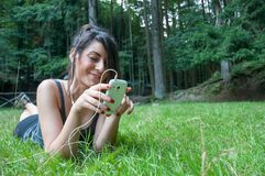 Beautiful girl play on smart phone on park Royalty Free Stock Photos
