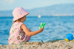 Beautiful girl playing. Beautiful little girl sitting and playing at the seacoast. Summer royalty free stock image