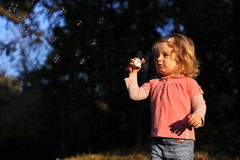Beautiful girl playing. Beautiful little girl playing with  soap bubbles Stock Photos