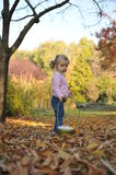 Beautiful girl playing. Beautiful little girl playing in an autumn park Stock Images