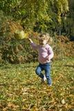 Beautiful girl playing. Beautiful little girl playing in an autumn park Stock Image