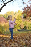 Beautiful girl playing. Beautiful little girl playing in an autumn park Royalty Free Stock Photo