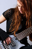 Beautiful girl playing bass guitar royalty free stock image