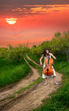 Beautiful girl playing the cello. On the road near trees at sunset background Royalty Free Stock Image