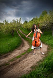 Beautiful girl playing the cello. On the road near trees at dramatic sky background Royalty Free Stock Image