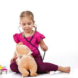 Beautiful girl playing doctor with a doll Stock Images