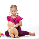Beautiful girl playing doctor with a doll Royalty Free Stock Images