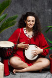 Beautiful girl playing drum in tropical plants over grey background. Royalty Free Stock Images