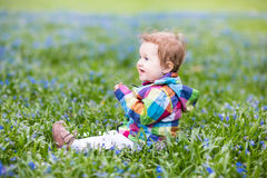 Beautiful girl playing among first blue flowers Royalty Free Stock Photo
