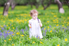 Beautiful girl playing with flowers in a garden Royalty Free Stock Photography