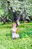 Beautiful girl playing with flowers in a garden Stock Images