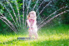 Beautiful girl playing with garden sprinkler. Funny laughing little girl in a colorful swimming suit running though garden sprinkler playing with water splashes stock photo