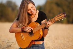 Beautiful girl playing the guitar Stock Image