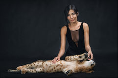 Beautiful girl playing with a lion cub on a black background. The Beautiful girl playing with a lion cub on a black background Royalty Free Stock Photography