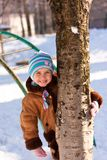 Beautiful girl playing near the tree in winter Royalty Free Stock Images