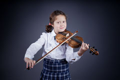 Beautiful girl playing the old violin on dark background Stock Photos