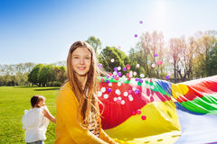 Beautiful girl playing parachute game with friends Royalty Free Stock Photo