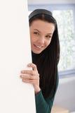 Beautiful girl playing peek-a-boo behind wall. Beautiful smiling girl playing peek-a-boo behind wall Stock Images