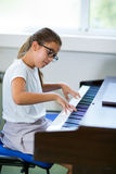 Beautiful girl playing the piano at the music school. Selective focus Stock Images