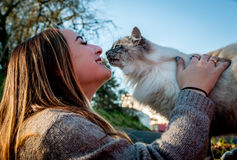 Beautiful girl playing with a rescued stray cat Stock Photography