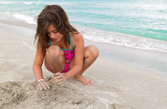 Beautiful girl playing with sand o a beach Stock Photos