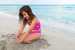 Beautiful girl playing with sand o a beach Stock Photo