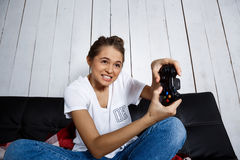 Beautiful girl playing video games, sitting on sofa at home. Royalty Free Stock Photography
